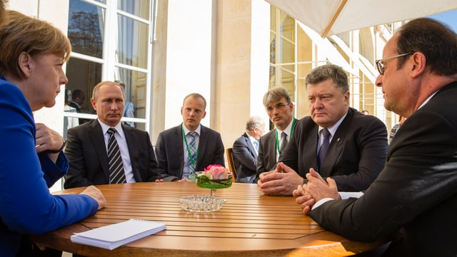Gespräche an einem runden Tisch zwischen Merkel, Putin, Poroschenko und Hollande.