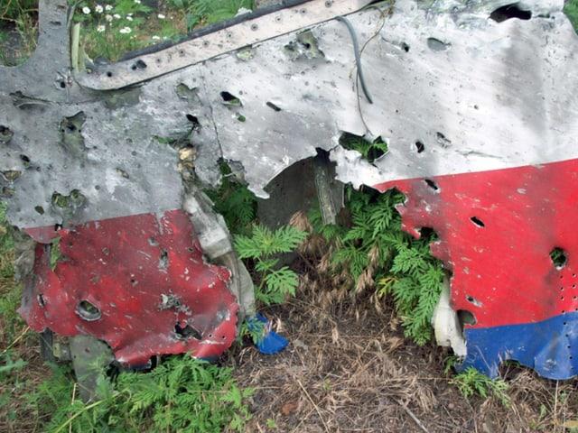 Ein Teil des Flugzeug-Wracks. Es ist von Löchern durchzogen.