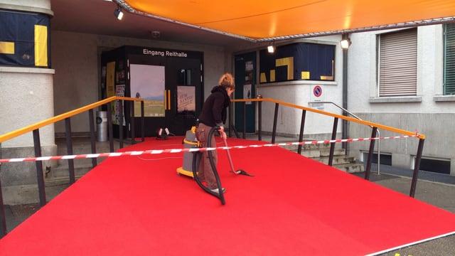 Roter Teppich wird gestaubsaugt, bevor die Prominenz zur Eröffnung eintrifft.