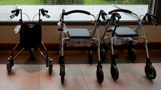 Drei Rollatoren stehen in einem Pflegeheim auf einem Parkettboden vor einem Fenster.