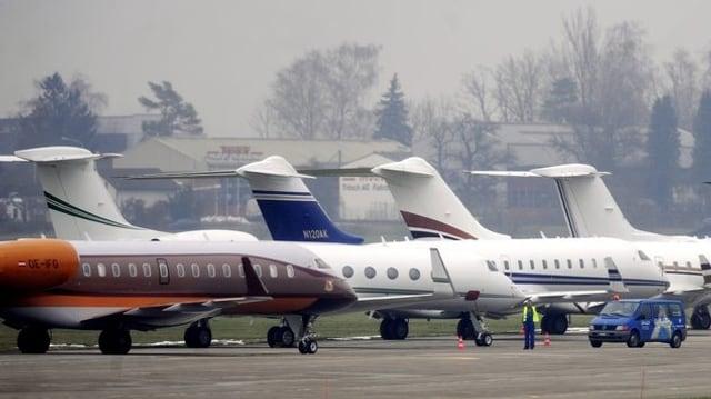 Vier Business-Jets stehen auf einem Rollfeld.