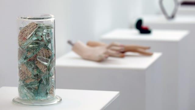 Ein Glas voller Scherben, Hände einer Puppe und weitere Objekte auf weissen Sockeln in einem Museum ausgestellt.