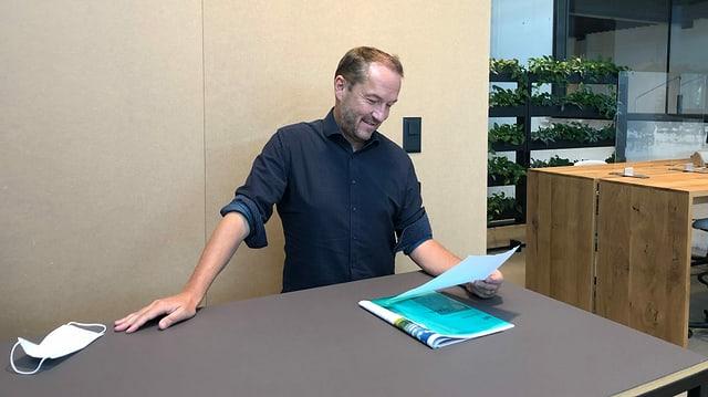 Ein Mann steht an einem Tisch und schaut sich Papiere an.