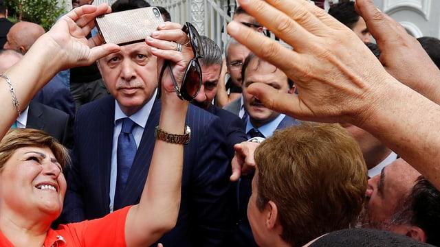 Eine Frau versuch ein Selfie mit Erdogan zu machen.