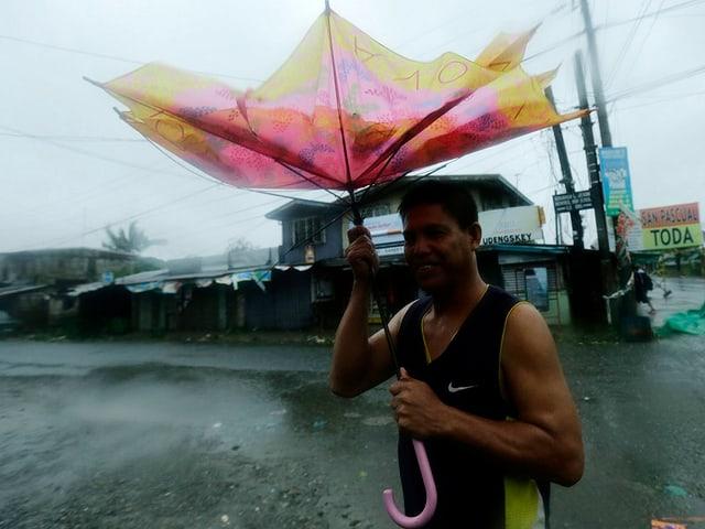 Mann hält einen zerzaustem rosa-gelben Regenschirm über sich