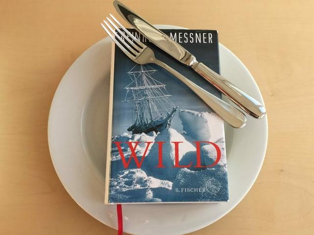 Der Abenteuerroman «Wild» von Reinhold Messner liegt auf einem weissen Teller. Messer und Gabel nebeneinander drüber.