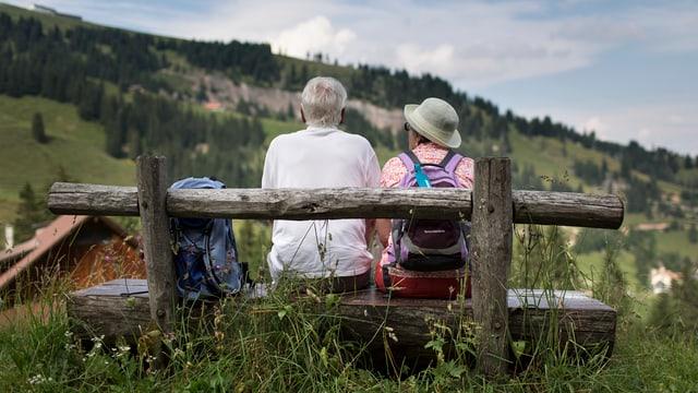 Rentnerpaar sitzt auf einer Bank mit Aussicht auf die Rigi.