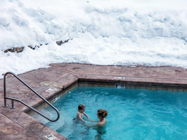 Frau mit kleinem Kind in Pool, daneben liegt Schnee