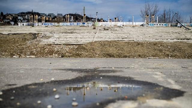 Die Ruine des Hardturmstadions in Zürich. Im Vordergrund eine Pfütze, im Hintergrund die baufälligen Stehtribünen.