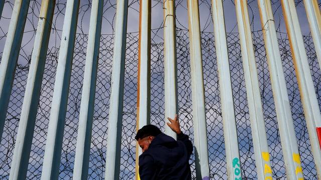 Mann steht an der Mauer am Strand von Tijuana, Mexiko