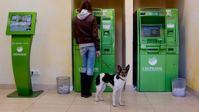 Eine Frau mit einem Hund an einer Leine bezieht Geld an einem grünen Bankomaten.
