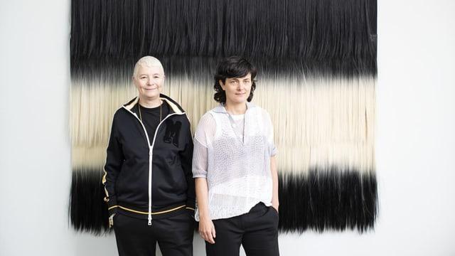 Porträt von Pauline Boudry und Renate Lorenz vor gestreift schwarz-weissem Aushang