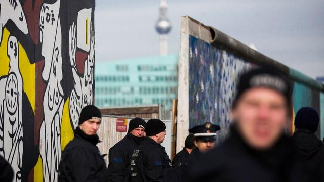 Polizisten vor einer Lücke in der Berliner Mauer.
