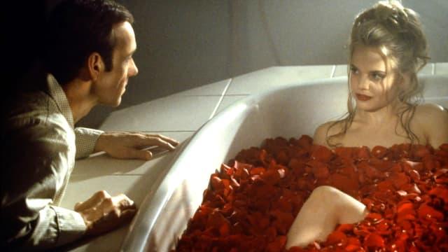 Eine junge Frau liegt in einer Badewanne voller roter Rosenblätter, daneben kniet ein Mann.