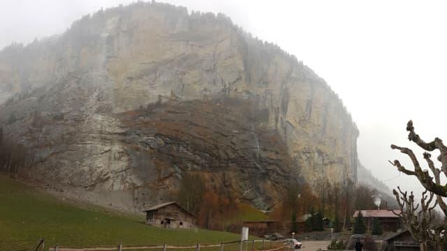 Felswand mit Bauernhäusern im Vordergrund