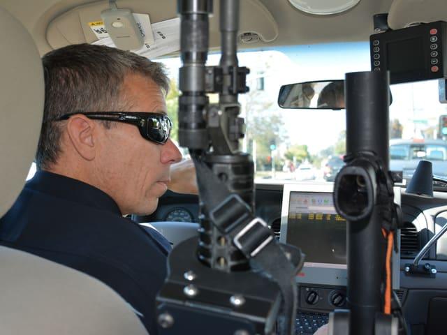 Brent Northrup sitzt mit dunkler Sonnenbrille im Auto, neben ihm sieht man seine beiden Gewehre.