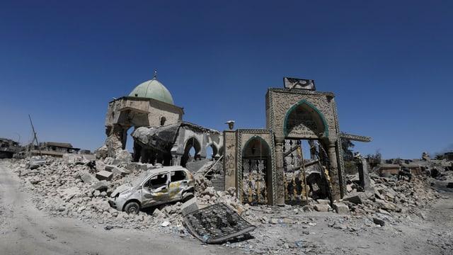 Ruine und Trümmerhaufen unter blauem Himmel.