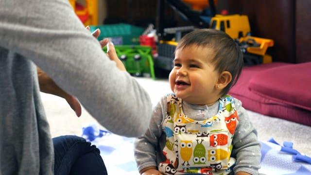 Eine Mutter macht ein Fingerspiel mit ihrem Kleinkind.