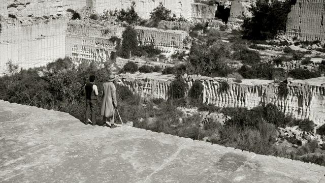 Zwei Männer stehen vor einem Abgrund.