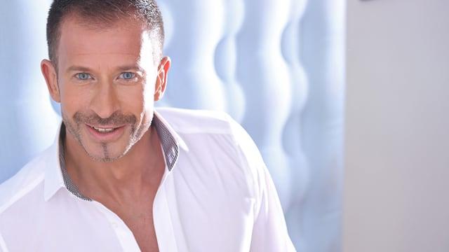 Porträtbild von Leonard mit weissem Hemd vor hellblauem Hintergrund.