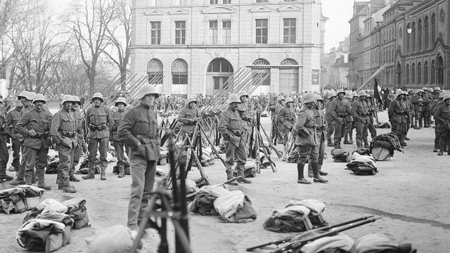 Soldaten stehen auf einem Platz. Überall sind Gewehre gestapelt.