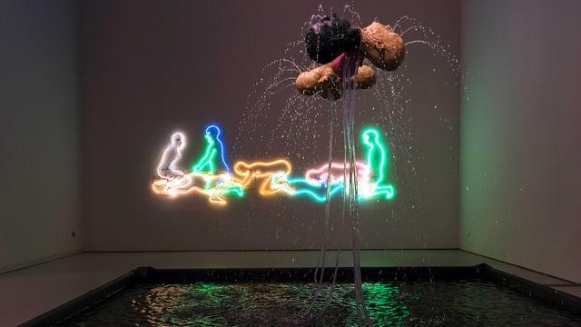 Mit Neonröhren geformte Umrisse von Menschen an einer Wand
