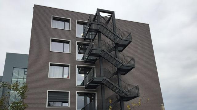 Mehrstöckiges Gebäude mit Feuerleiter.