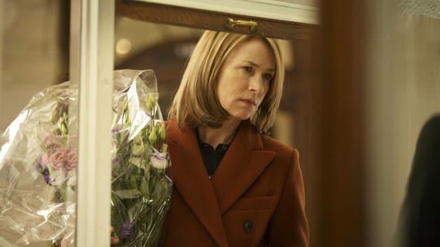 Filmstill: Eine Frau mit einem Blumenstrauss.