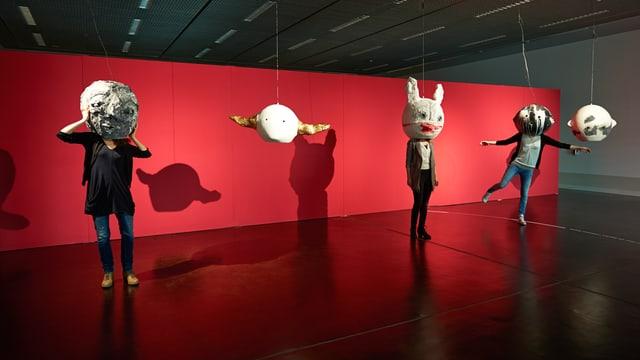 Ausstellungsraum: Vor einer Wand stehen drei Figuren mit riesigen, kugelrunden Köpfen.
