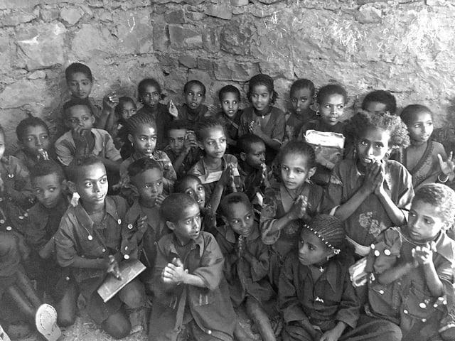 Schwarz-weiss-Foto: Kinder sitzen am Boden in einer Ecke.