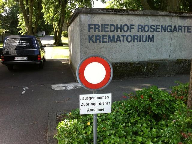 """Der Eingang zum Freidhof Rosengarten. In der Einfahrt steht der Leichenwagen des """"Bestattungsinstitut Conrad""""."""