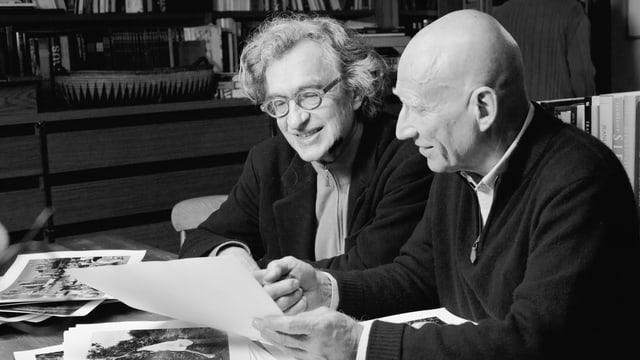 Regisseur Wim Wenders spricht mit Fotograf Sebastião Salgado sitzend über seine Bilder.