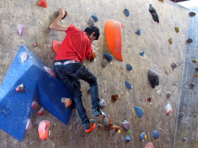 Ein junger Mann in Jeans und rotem T-Shirt an einer Kletterwand