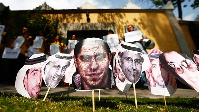 Schilder mit verschiedenen Menschenköpfen stecken im Gras vor einem Haus.