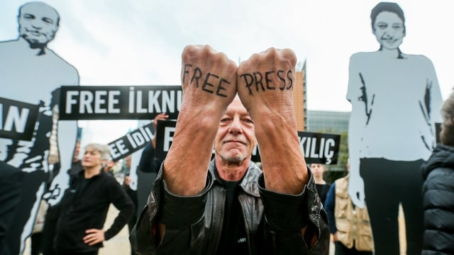 Mann hat auf seine zwei Handrücken «Free Press» geschrieben.