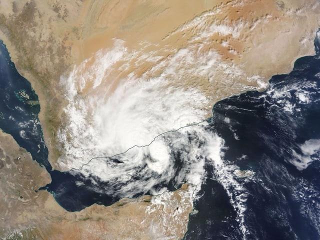 Die weisse Wirbelstruktur des Sturms ist nach wie vor zu sehen, doch fehlt die trichterförmige Vertiefung im Zentrum. Um den Sturm herum sieht man auf dem Satellitenbild die Wüstenlandschaft.