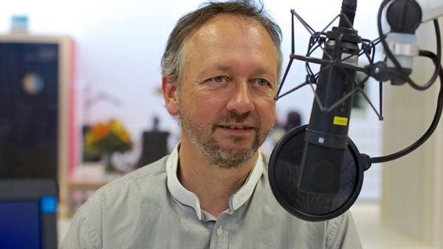 Porträt Thomas Merz vor einem Radiostudio-Mikrofon.