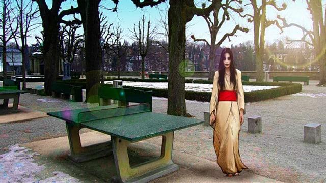Eine blasse Frau in weissem Kleid und mit dunklen Augen steht neben einem Ping-Pong-Tisch auf einem grossen Platz.