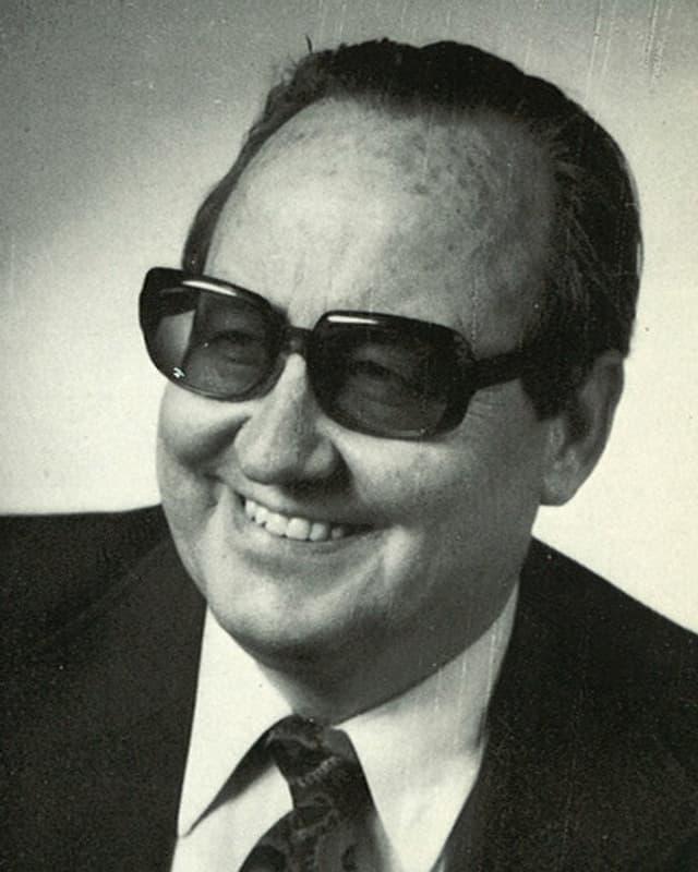 Schwarz-weisse Fotografie mit Porträt von Jost Marty mit Anzug und Krawatte und grosser dunkler Brille.