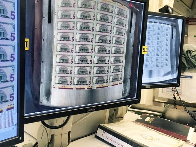 Drei Monitore: darauf zu sehen sind Dollarnoten.