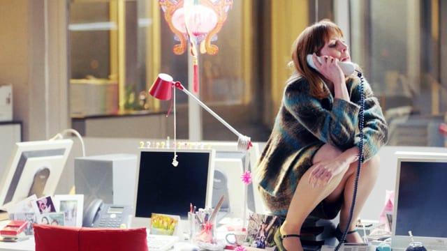 Eine Frau sitzt auf einem Schreibtisch und telefoniert.