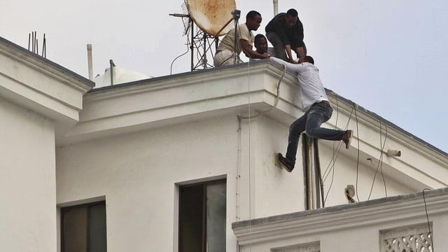 Gäste des angegriffenen Hotels retten sich auf ein Dach.