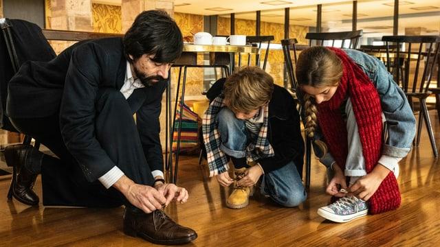 Eine Familie am Boden: alle binden sich die Schuhe.