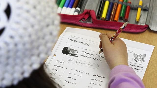 Ein Mädchen schreibt im Türkischunterricht in Deutschland Vokabeln auf.