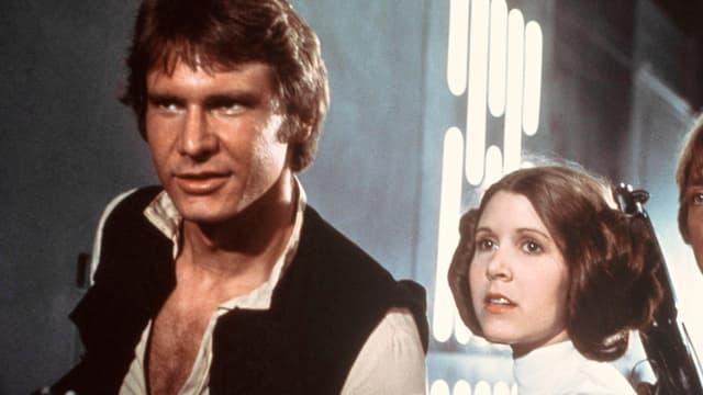 Ein Standbild aus Starwars zeigt Han Solo (Harrison Ford) zusammen mit Prinzessin Leia (Carrie Fisher)