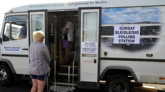 Eine Frau wartet vor einem zum Wahllokal umfunktionierten Bus.