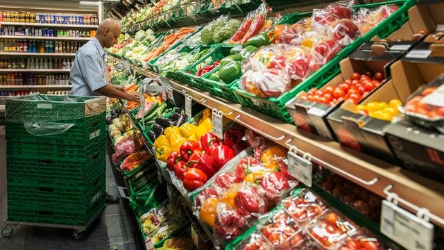 Ein Coop-Mitarbeiter räumt ein Gemüseregal ein.