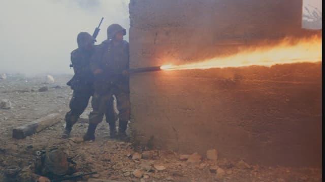 Zwei Soldaten verstecken sich hinter einer Mauer und feuern aus einem Flammenwerfer um die Ecke.