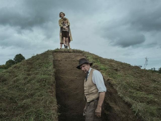 Ein Mann steht am Fusse eines Grabs. Oben dran steht eine Mutter mit ihrem Sohn.
