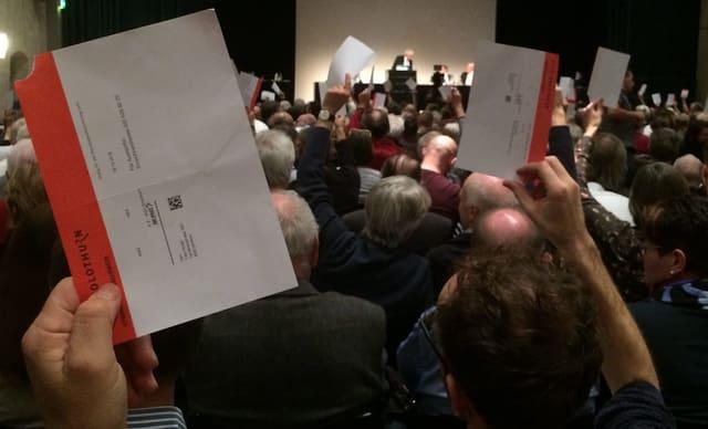 Menschen halten Stimmkarten in die Höhe an der Gemeindeversammlung in Solothurn